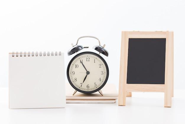 Calendrier vierge et tableau noir et heure de l'horloge à cinq minutes à sept heures sur blanc