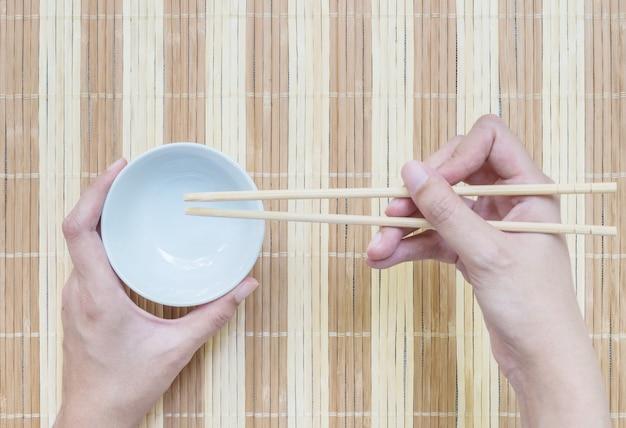 Calice en céramique agrandi avec des baguettes dans la main de la femme sur fond de tapis en bois