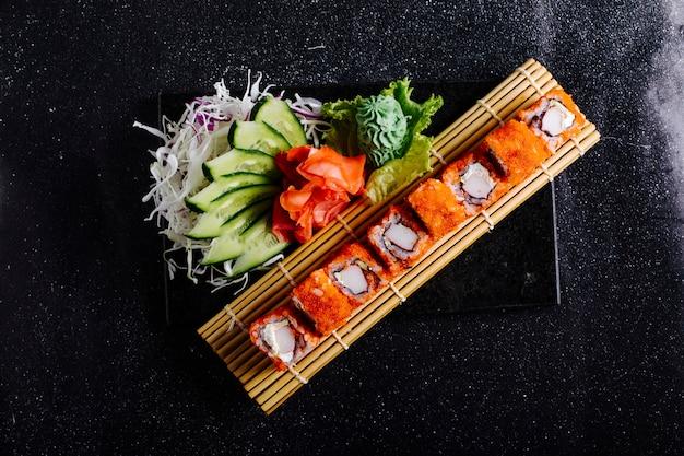 La californie chaude roule sur un tapis de sushi avec du wasabi, du gingembre rouge et du concombre.