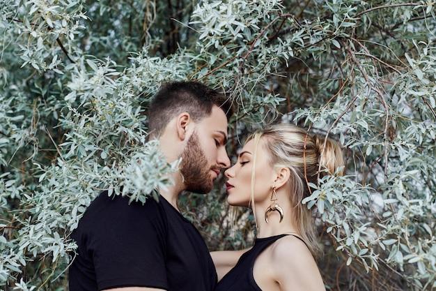 Câlins et baiser couple amoureux dans les branches de buissons