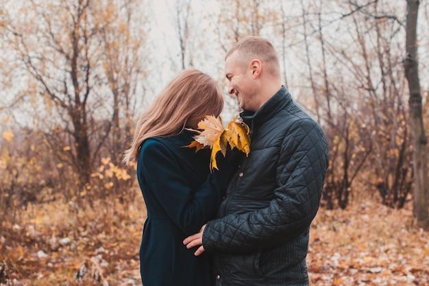 Câlins douillets affectueux de jeune couple d'amoureux dans le parc d'automne