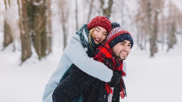 Câlins heureux couple dans les chutes de neige
