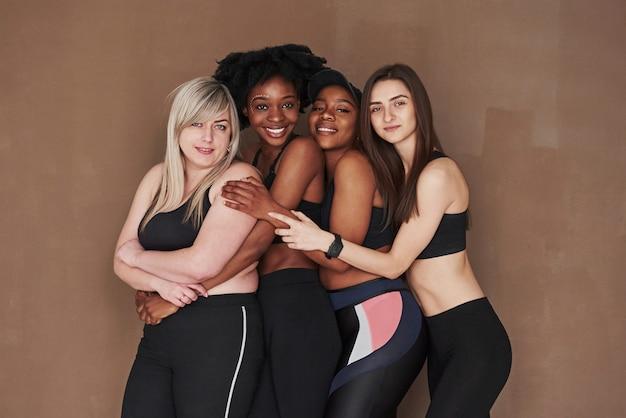 Des câlins et des sourires. groupe de femmes multiethniques debout contre l'espace brun