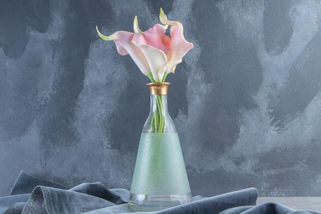 Calla lily dans une cruche sur un morceau de tissu, sur le fond de marbre. photo de haute qualité