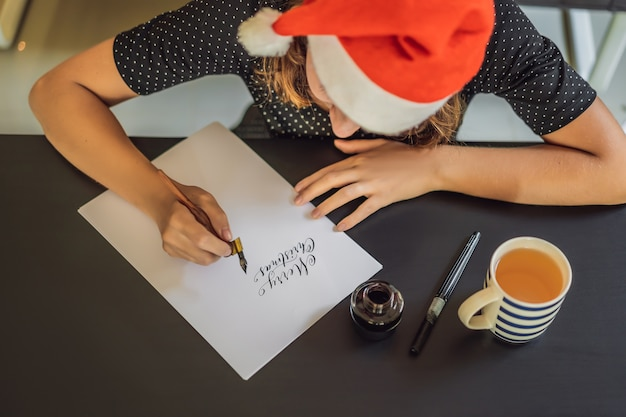 Calligraphe jeune femme écrit une phrase sur du papier blanc