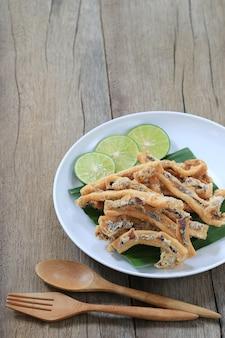 Calmars frits des fruits de mer thaïlandais dans le plat blanc sur le plancher de bois.