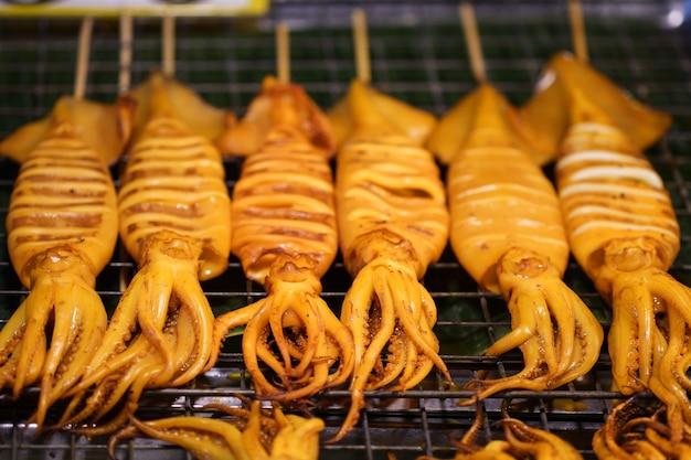 Calmars grillés placés sur un gril à vendre sur le marché.
