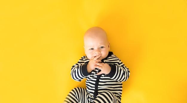 Calme bébé curieux couché sur fond jaune, regardant la caméra, vue du dessus, copiez l'espace