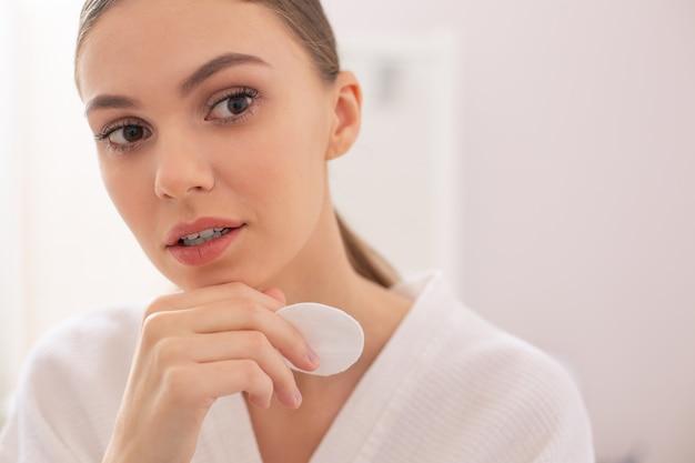 Calme belle jeune femme regardant pensivement au loin tout en tenant un coton près de son visage