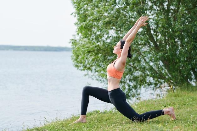 Calme concentré jeune femme en tenue de sport s'appuyant sur un genou et étirement du corps tout en faisant la pose du croissant sur la rive