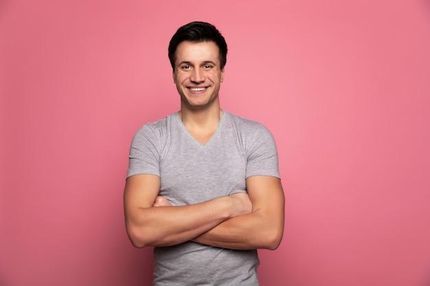 Calme et confiant. homme gai en t-shirt gris, debout, les bras croisés et regardant dans la caméra.