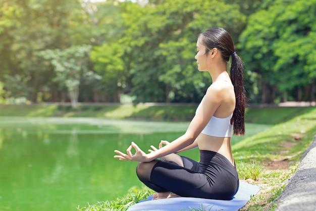 Calme et détente, les femmes asiatiques méditent tout en pratiquant le yoga dans un parc en plein air. concept de liberté bonheur de femme. image tonique vie saine