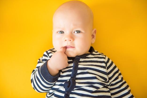 Calme enfant curieux tenant ses doigts dans sa bouche, allongé sur un fond jaune`` vue de dessus