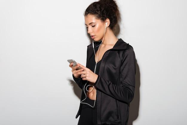 Calme femme brune bouclée de remise en forme, écouter de la musique et à l'aide de smartphone