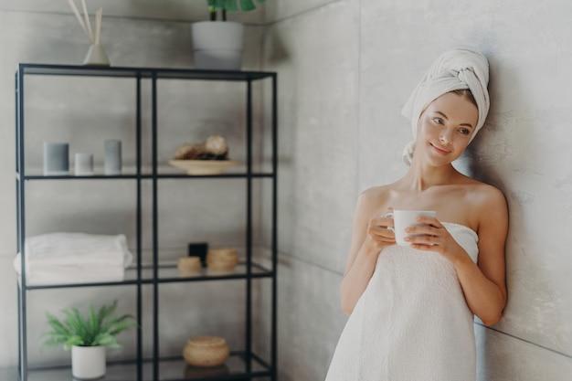 Calme femme détendue pose dans une serviette contre l'intérieur de la salle de bain, enveloppée dans une serviette de bain