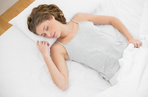 Calme femme mince couchée sur son lit sous la couverture