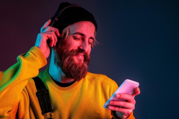 Calme, heureux, utilisant le téléphone. portrait de l'homme caucasien sur l'espace dégradé en néon