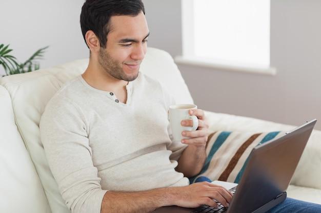 Calme homme séduisant, buvant du café tout en travaillant sur son ordinateur portable