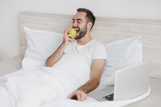 Calme jeune bel homme barbu allongé dans son lit avec une couverture d'oreiller en drap blanc dans la chambre à la maison