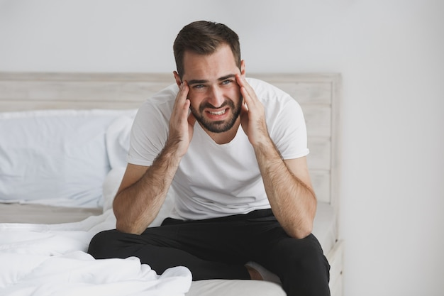 Calme jeune bel homme barbu assis dans son lit avec une couverture d'oreiller en drap blanc dans la chambre à la maison