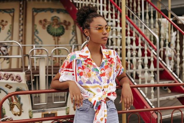Calme jeune femme brune bouclée en pantalon denim, chemisier coloré et lunettes de soleil orange détourne le regard et se penche sur le carrousel à l'extérieur