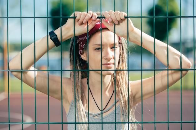 Calme jeune femme réfléchie avec des dreadlocks légèrement souriant et vous regarde à travers la clôture à mailles de chaîne