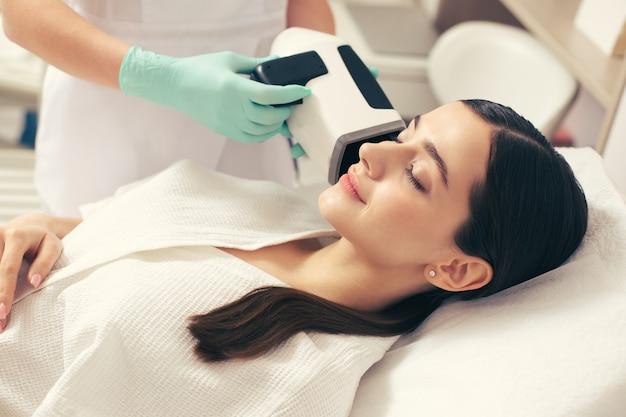 Calme jeune femme souriante les yeux fermés tandis que l'esthéticienne dans des gants en caoutchouc tenant une caméra d'analyse de la peau près de son visage