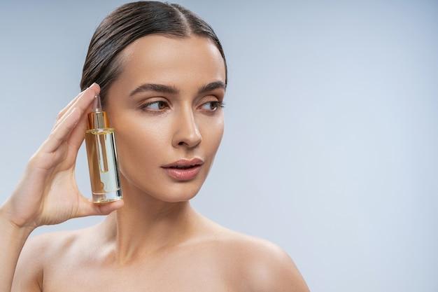 Calme jeune femme utilisant un traitement cosmétique pour le visage
