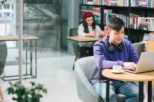 Calme jeune homme asiatique à l'aide d'un ordinateur portable moderne assis avec une tasse de café à la petite table