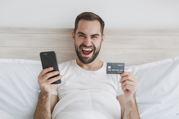 Calme jeune homme barbu allongé dans son lit avec une couverture d'oreiller en drap blanc dans la chambre à la maison