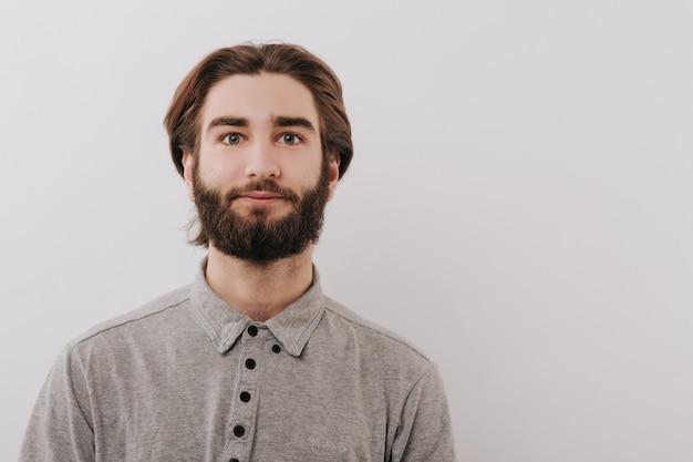 Calme jeune homme, à la recherche dans l'appareil photo, studio, espace gris isolé, copie espace, gros plan