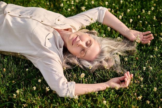 Calme. jolie femme aux cheveux gris satisfaite en chemisier léger somnolant sur une pelouse en fleurs le jour d'été