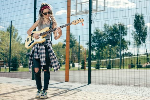 Calme jolie jeune femme avec des dreadlocks debout à côté de la clôture à mailles de chaîne sur le terrain de sport et jouer de la guitare tout en étant seul