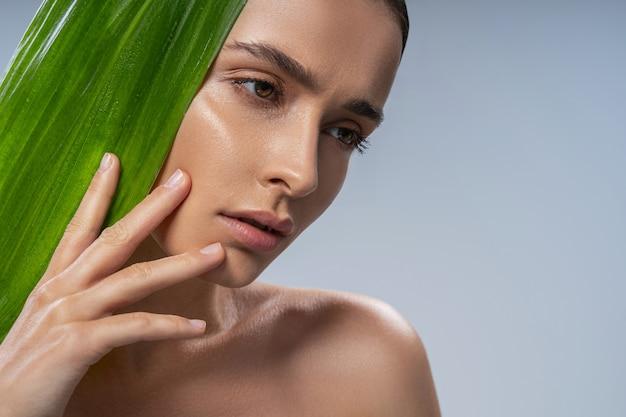 Calme jolie jeune femme avec plante verte