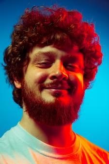 Calme, ravi. caucasien bouchent le portrait de l'homme isolé sur un mur bleu en néon rouge. beau modèle masculin, cheveux bouclés rouges. concept d'émotions humaines, expression faciale, ventes, publicité.