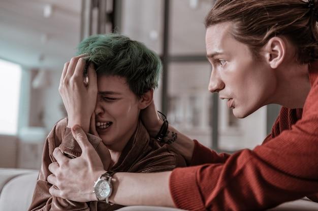 Calmer. mari émotif inquiet calmant sa femme qui pleure avec le nez qui saigne
