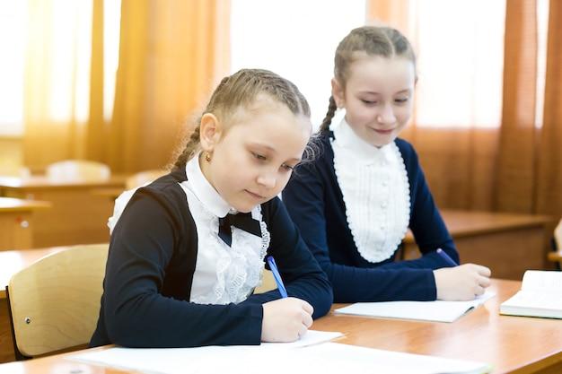 Une camarade de classe regarde dans le cahier de quelqu'un d'autre.