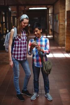 Camarades de classe à l'aide de téléphone portable dans le couloir de l'école