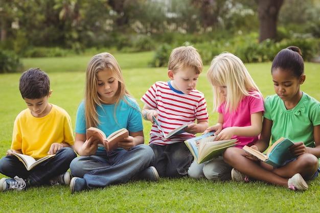 Camarades de classe assis dans l'herbe et lire des livres