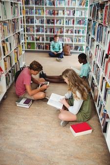 Des camarades de classe attentifs qui étudient en bibliothèque