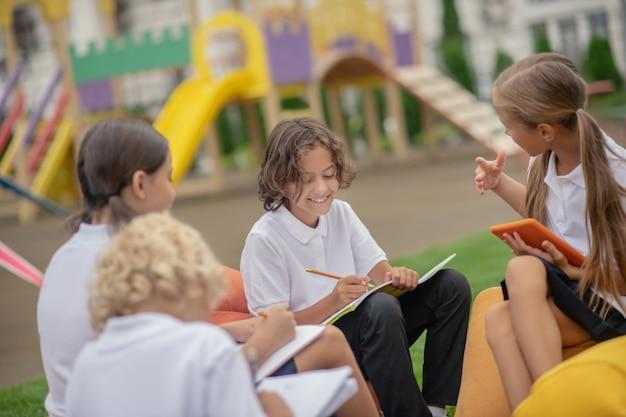 Camarades de classe. groupe d'élèves assis à l'extérieur et préparant leurs devoirs