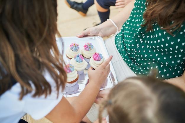 Des camarades de classe prenant des cupcakes sur un plateau tenu par l'enseignant