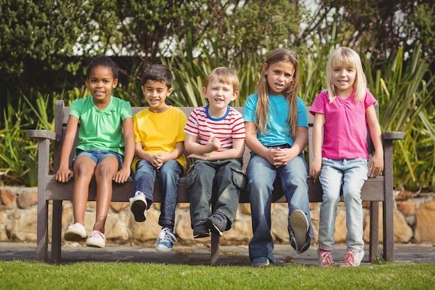 Camarades de classe souriants assis sur un banc