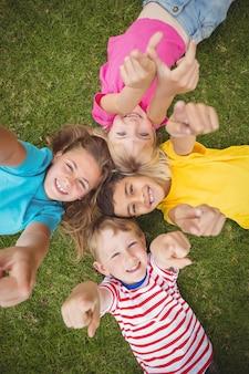 Camarades de classe souriants couché dans l'herbe et pointant vers la caméra
