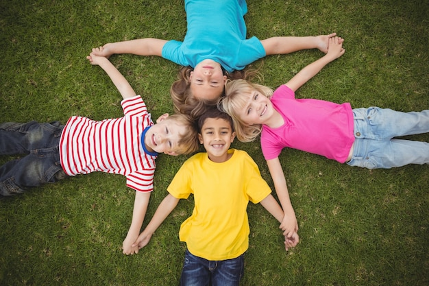 Camarades de classe souriants dans l'herbe et main dans la main