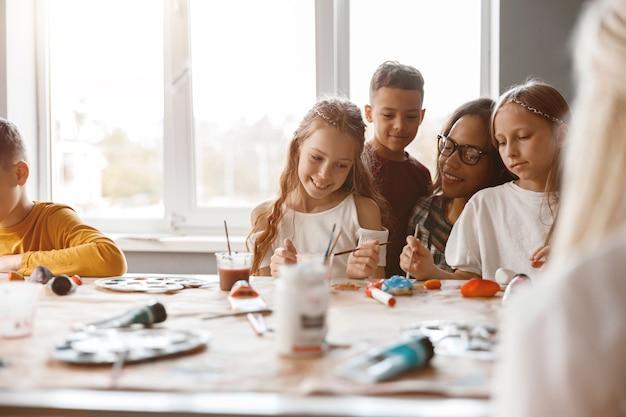 Des camarades de classe souriants faisant de la peinture d'art à l'aide d'aquarelles