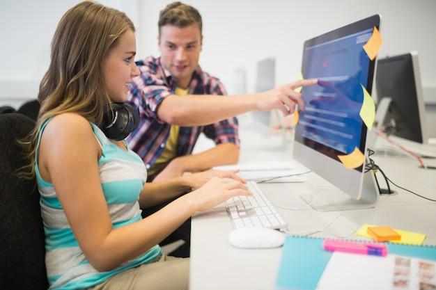 Camarades de classe souriants faisant une tâche ensemble dans la salle informatique
