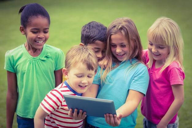 Camarades de classe souriants avec tablette ensemble