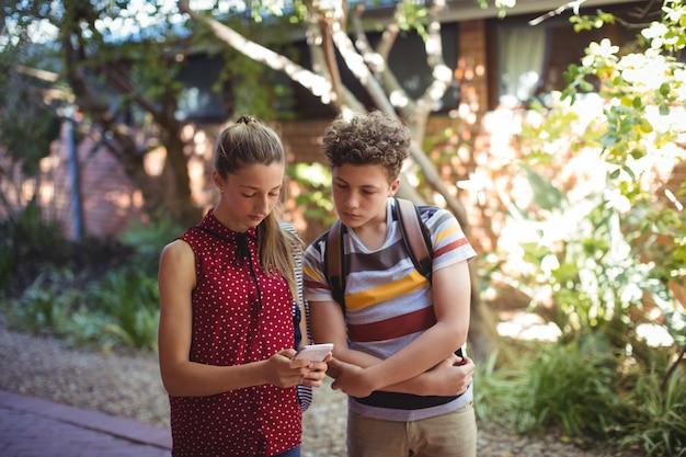 Camarades de classe utilisant un téléphone portable