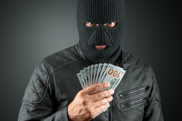 Cambrioleur dans une cagoule détient des dollars dans ses mains sur un fond sombre